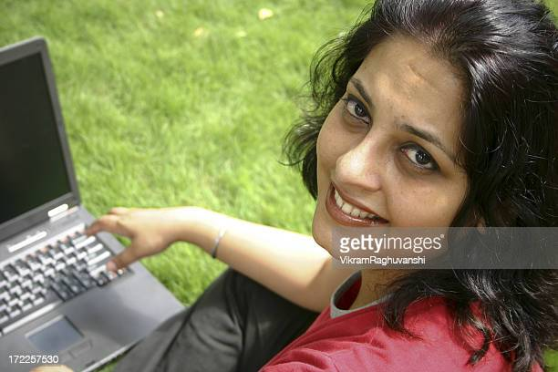 One Cheerful Indian woman with Laptop sitting office lawn Worker