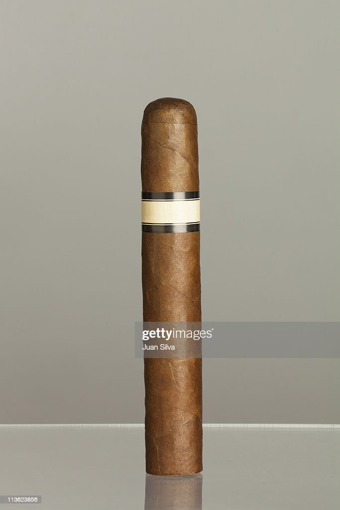 One cigar standing on reflective surface
