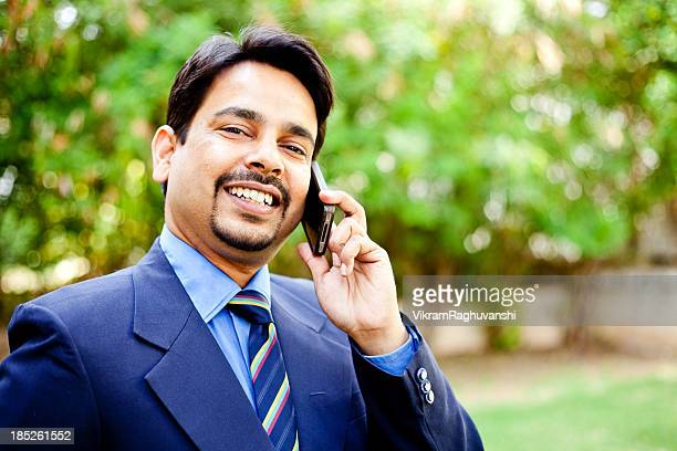 One Confident Cheerful Indian Businessman Talking on the Phone Outdoors