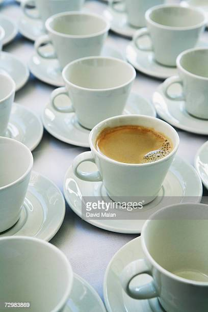 One cup of coffee amongst empty cups, elevated view