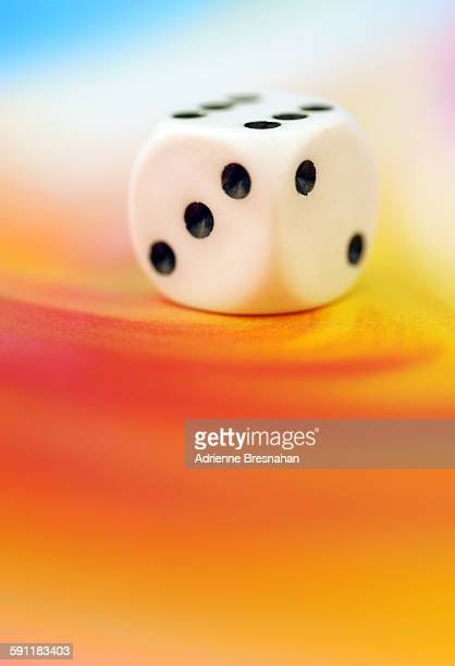 One die on a colorful background
