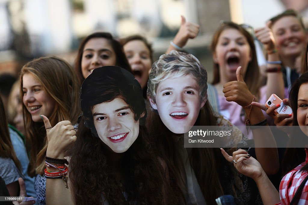 One Direction fans take their positions in Leicester Square ahead of the premier to the bands new film on August 20, 2013 in London, England. The bands new film, 'This Is Us', will premier this evening at the Empire cinema.