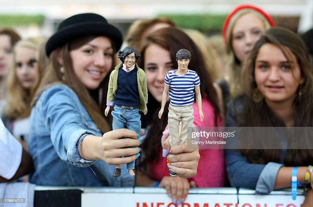 One Direction fans who have gathered for the One Direction Premiere 'This Is Us' hold up their One Direction dolls at the Empire Cinema, Leicester Square on August 20, 2013 in London, England.