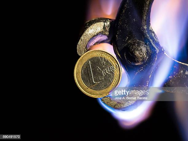 One euro coin held with pliers on fire