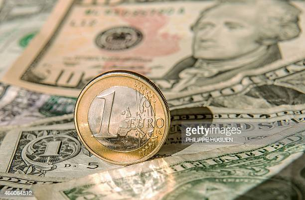 A one euro coin is pictured on one US dollar notes on March 13 2015 in Godewaersvelde Northern France AFP PHOTO / PHILIPPE HUGUEN / AFP / PHILIPPE...