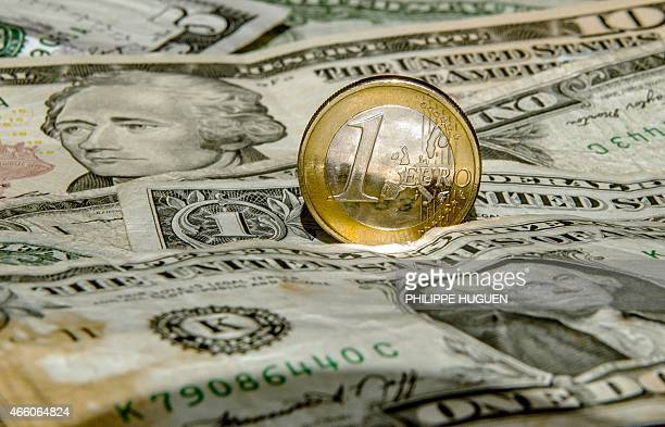 A one euro coin is pictured on one US dollar notes on March 13 2015 in Godewaersvelde Northern France AFP PHOTO / PHILIPPE HUGUEN