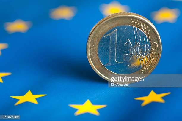 One euro coin with blue & yellow star background