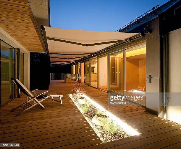 One family house, wooden terrace with awnings in the evening