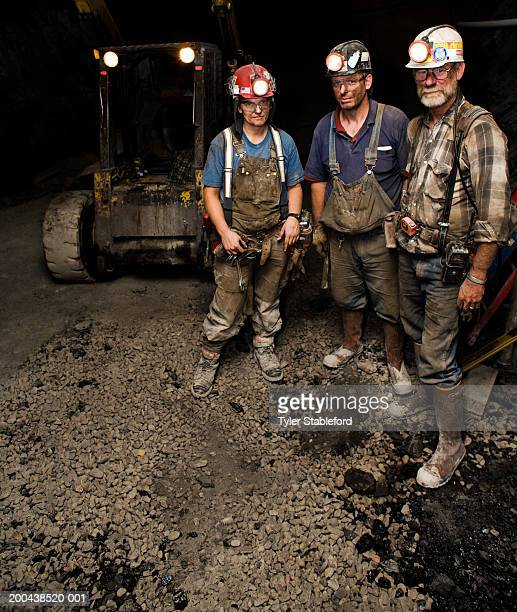One female and two male coal miners near forklift in mine, portrait
