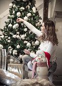 One girl decorating Christmas tree