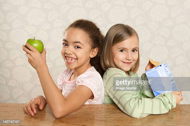 Ein Mädchen und ein Apfel und ein Mädchen mit einer Packung von Chips