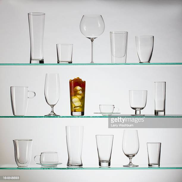 One glass filled with bubble tea placed amongst a collection of empty drinking glasses