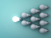 One glowing light bulb standing out from the unlit incandescent bulbs on green background , leadership and different concept . 3D rendering.