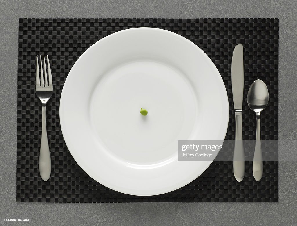 One green pea on white plate with table setting, elevated view : Stock Photo