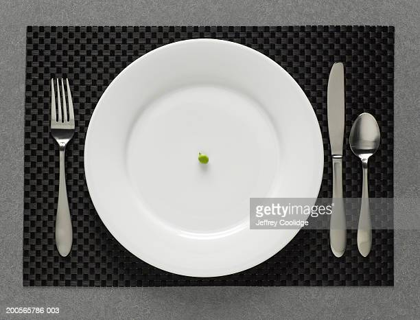 One green pea on white plate with table setting, elevated view