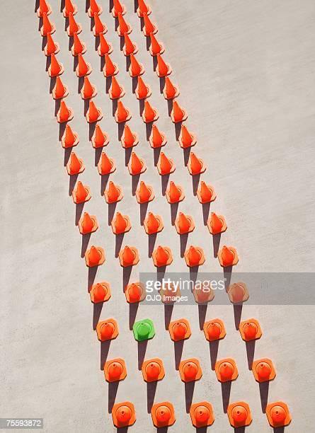 One green pylon amid seventy-four orange pylons