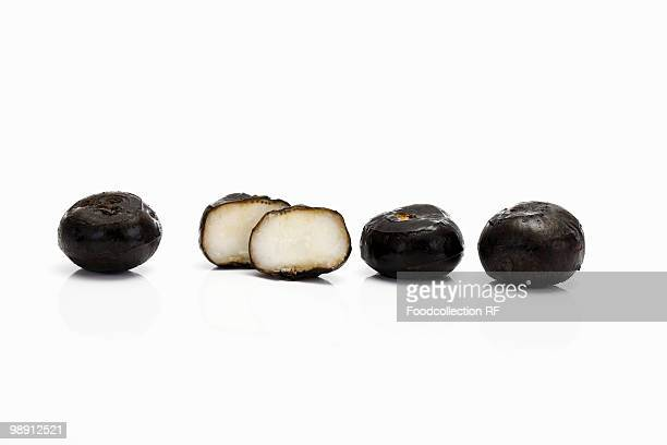 One halved and whole water chestnuts, close-up