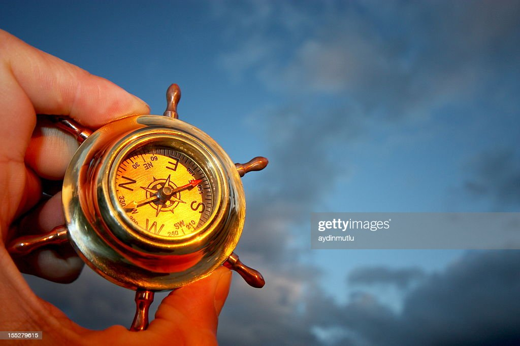 One hand holding a compass and a cloudy sky