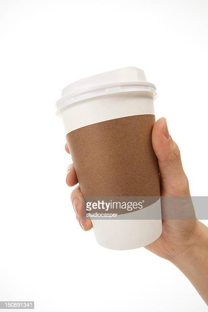 One hand holding white coffee cup with brown cup holder
