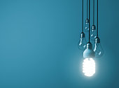 One hanging eco energy saving light bulb glowing and standing out from unlit incandescent bulbs on dark green pastel color background , leadership and different creative idea concept. 3D rendering.