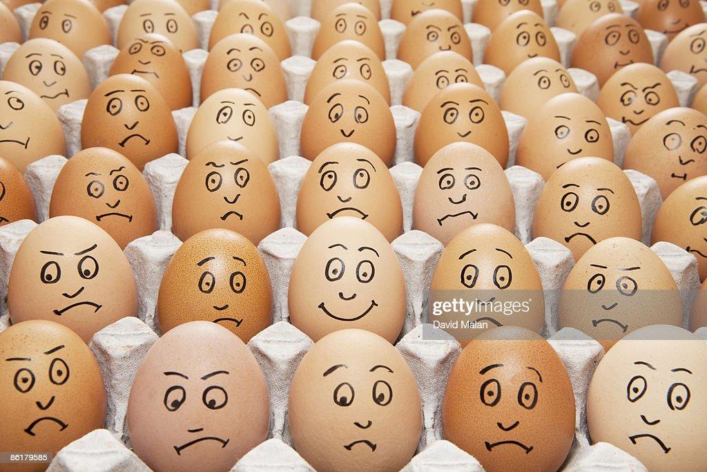 one happy egg amongst sad eggs : Stock Photo