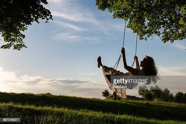 one happy young woman swinging outdoor at sunset