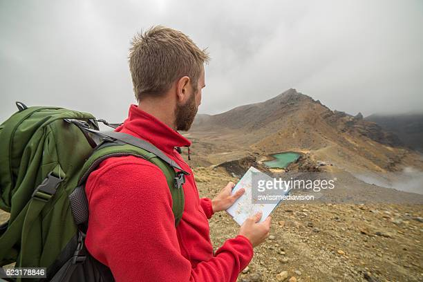 One hiker looks at map for directions-New Zealand