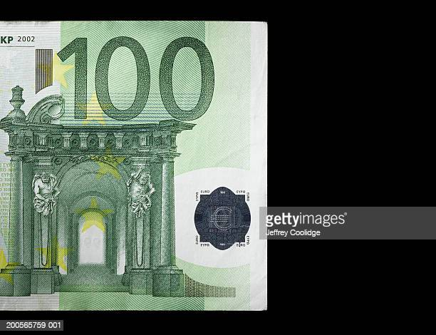 One hundred Euro note against black background, close-up