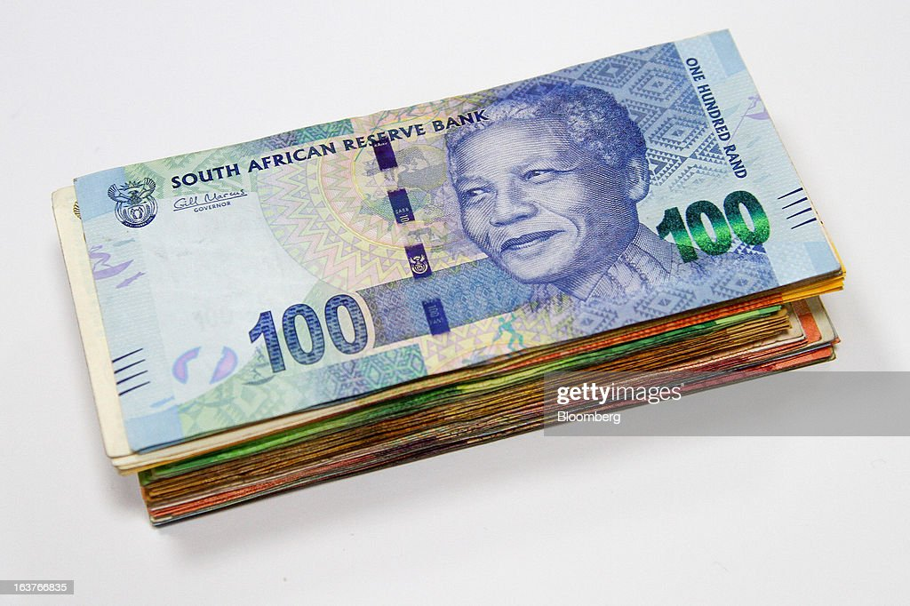 A one hundred rand currency banknote sits on top of a bundle of mixed denomination notes in this arranged photograph at a First National Bank (FNB) branch in Johannesburg, South Africa, on Friday, March 15, 2013. A recovery in mining and manufacturing is giving South Africa's rand and bonds a breather amid concern that growth is slowing while inflation accelerates. Photographer: Nadine Hutton/Bloomberg via Getty Images