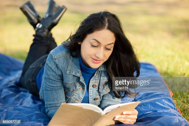 One Latin descent woman reading outdoors in park.