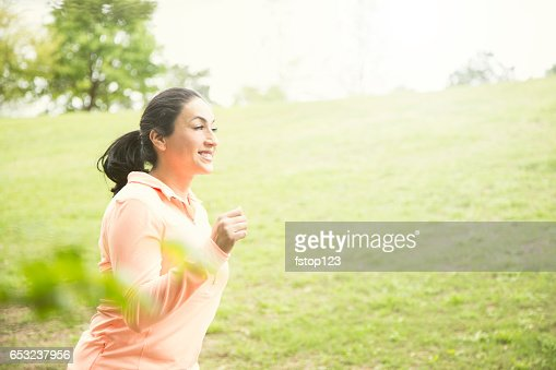 One Latin descent woman running in neighborhood park. : ストックフォト