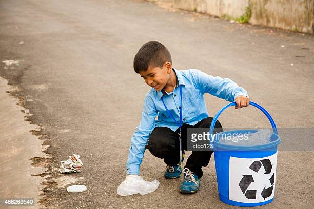 One little boy picking up trash to recycle. Roadside setting.