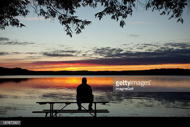 One Lonely Man Watching the Sunset Over Lake