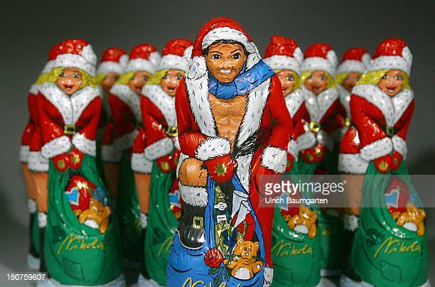 One male chocolate Santa Claus in front of a group of female chocolate Santa Clauses