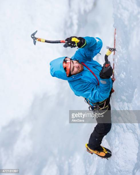 One Male Ice climber climbing  frozen cascade