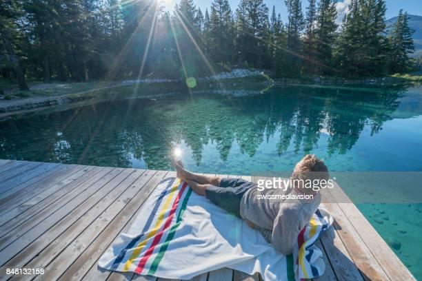One male lying on lake pier at sunrise