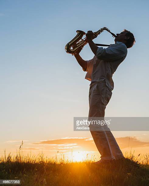 one male playing saxophone outdoor at sunset