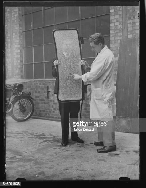 One man holds up the sheet of safety windscreen glass while another points to the place where a bullet was fired at it during tests at a glass...