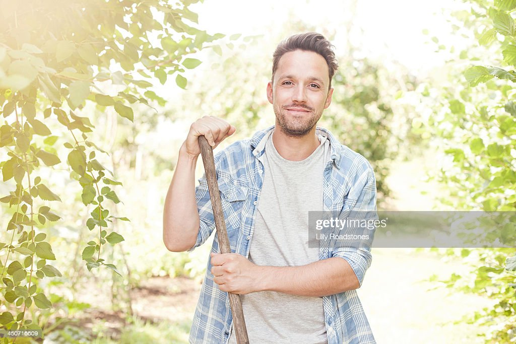 One man leaning on hoe in allotment : Stock Photo