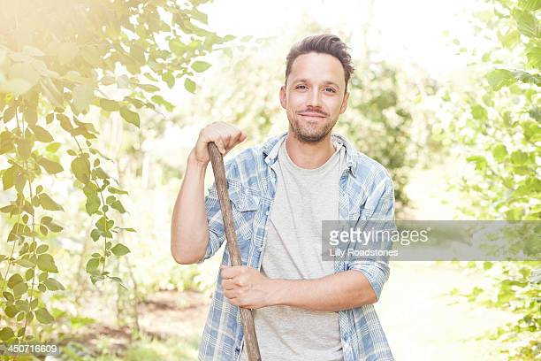 One man leaning on hoe in allotment