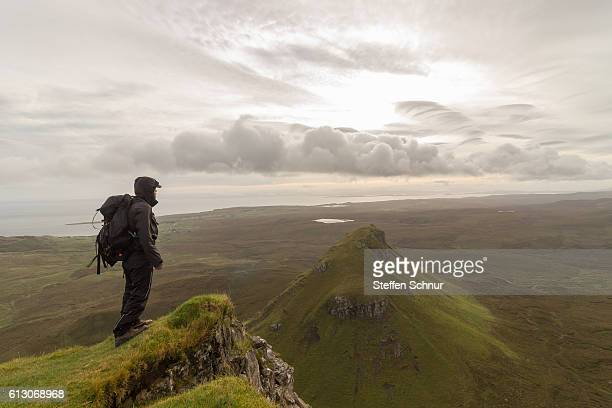 one man on mountain looking over the landscape with clouds Male hiker