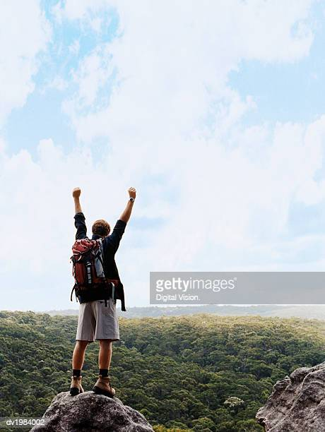 One Man Standing on Top of a Rock With his Arms Up