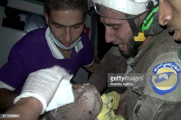 A one month baby is being taken to hospital by civil defence members after he was pulled out from the wreckage of a building hit by Assad regime...