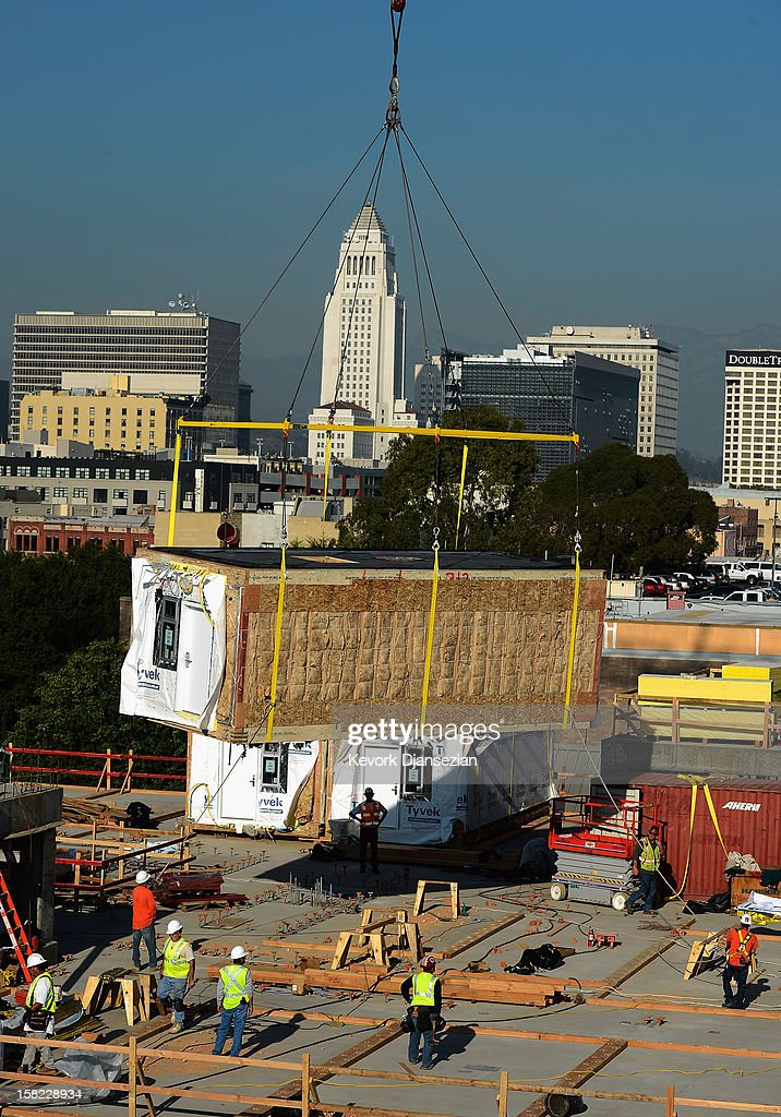 One of 102 prefabricated housing units is hoisted and placed atop the second floor of the Star Apartments building under construction by the Skid Row Housing Trust December 11, 2012 in Los Angeles, California. The modular homes will become the first multi unit prefabricated homes in Los Angeles for formerly homeless and impoverished people.