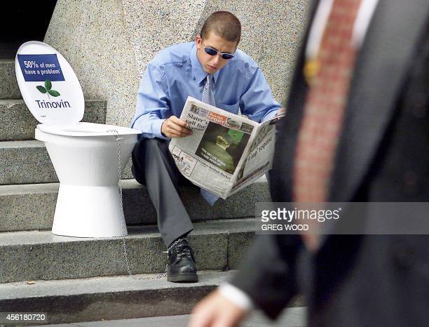 One of 50 males chained to toilets to help promote awareness for prostate and urinary disorders sits reading a newspaper in Martin Place Sydney 27...