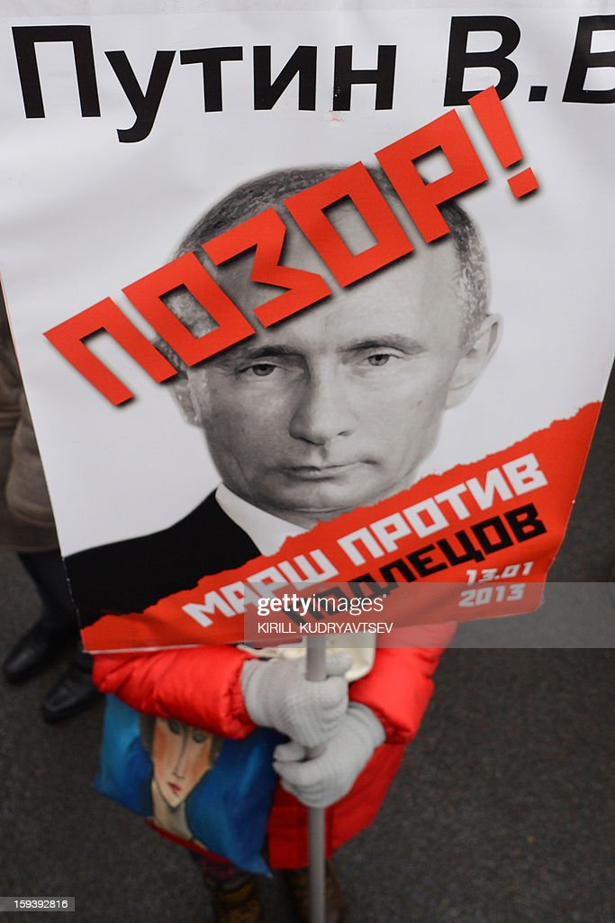 One of at least 20,000 Russian opposition supporters rallies on January 13, 2013 with a placard bearing a photo of President Valdimir Putin on the Boulevard Ring in the center of Moscow against a Kremlin law that banned US adoptions of Russian orphans. The protest dubbed 'the March Against Scoundrels' was aimed at naming and shaming the lawmakers who fast-tracked the anti-adoption bill through the lower house parliament, the State Duma.