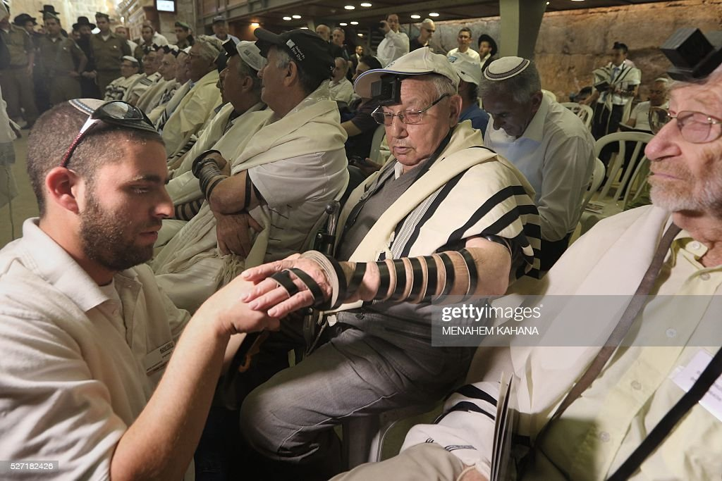 One of dozens Jewish holocaust survivors is helped to put on the Tefilin or the Phylacteries as they perform their Bar-Mitzvah Jewish ceremony, normally done at the age of 13-years-old, on May 2, 2016, at the Western Wall in the Jerusalem's Old City. Some 50 male and female holocaust survivors were invited to perform the Jewish Bar-Mitzvah ceremony some 70 years after World War II. / AFP / MENAHEM