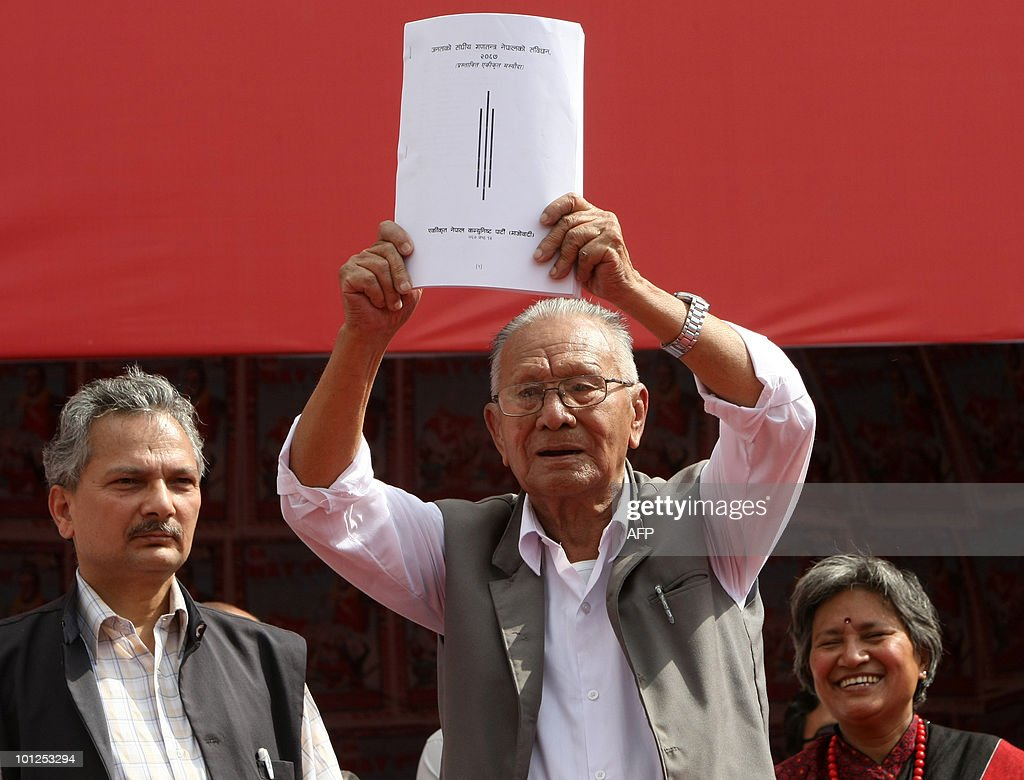 One of four remaining founders of the Nepalese Communist party Nar Bahadur Karmacharya shows the Maoist version of a draft constitution to the crowd during celebrations of the second anniversary of Republic Day in Kathmandu on May 29, 2010. Maoist vice-chairman and chief ideologue Baburam Bhattarai (here seen on the left) wrote the version. The 240-year old Hindu monarchy was abolished by the 601-member constituent assembly a year ago making Nepal the world's youngest republic. The CA could not complete the constitution writing in stipulated two-years time and so extended the term by one year last night. AFP PHOTO/Prakash MATHEMA