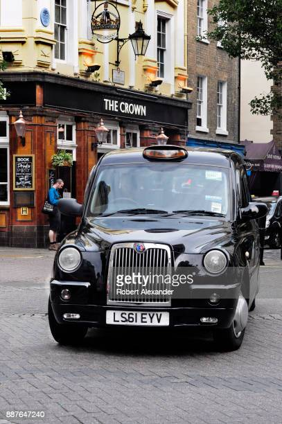 One of London England's iconic black cabs looks for a customer as he drives past The Crown pub