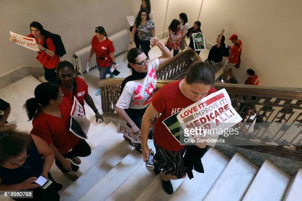 One of many groups protesting against the Republican health care repeal and replace legislation move through the Russell Senate Office Building on...